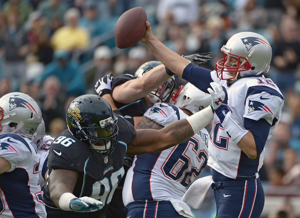Photo - New England Patriots quarterback Tom Brady, right, makes a move to get away from Jacksonville Jaguars defensive tackle Terrance Knighton (96) during the first half of an NFL football game on Sunday, Dec.  23, 2012, in Jacksonville, Fla. The Patriots won the game 23-16. (AP Photo/Phelan M. Ebenhack)