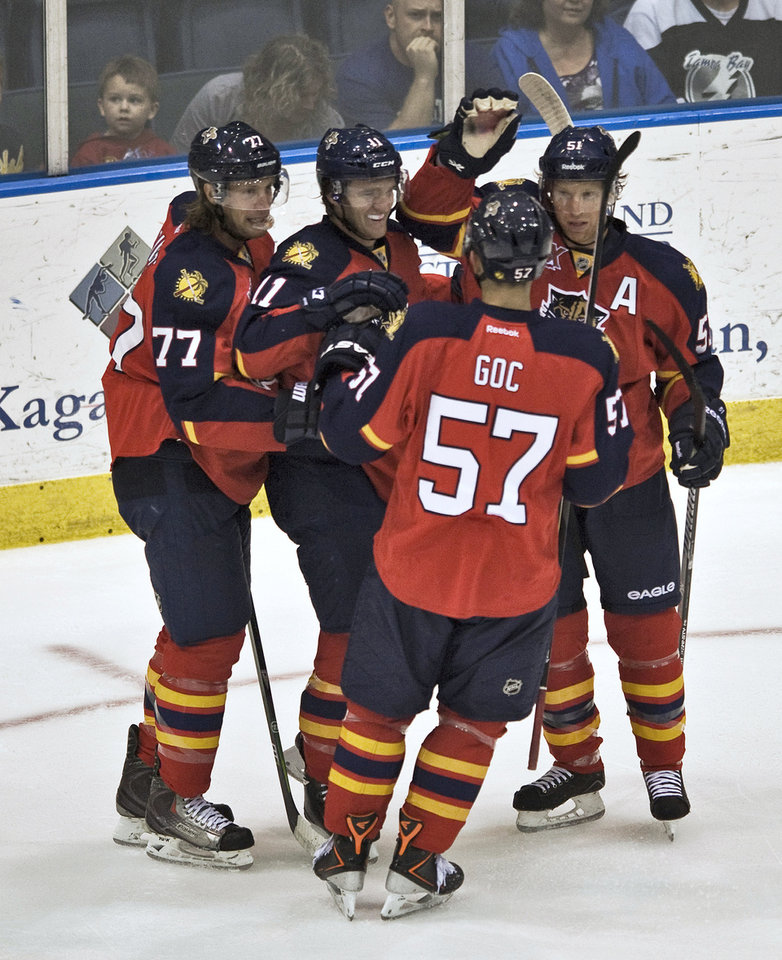 Photo - Florida Panthers' Tom Gilbert (77), Jonathan Huberdeau (11), Marcel Goc (57) and Brian Campbell, right, celebrate Huberdeau's goal against the Tampa Bay Lightning during the first period of an NHL preseason hockey game Thursday, Sept. 26, 2013, in Estero, Fla. (AP Photo/Steve Nesius)