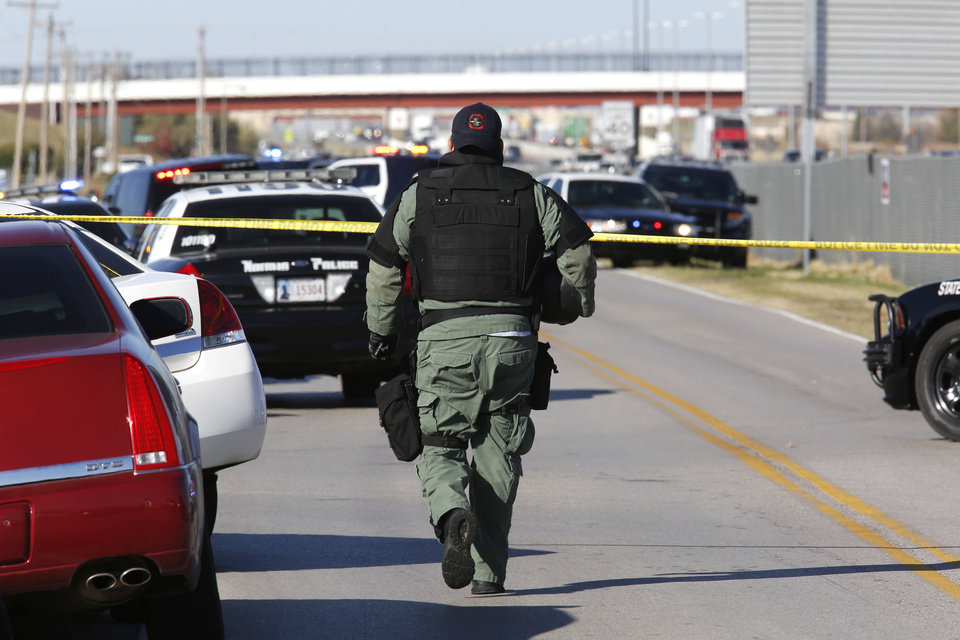 Photo - A SWAT member arrives on the scene of a hostage situation at Nextep in Norman Monday, Nov. 10, 2014.  Photo by Paul B. Southerland, The Oklahoman