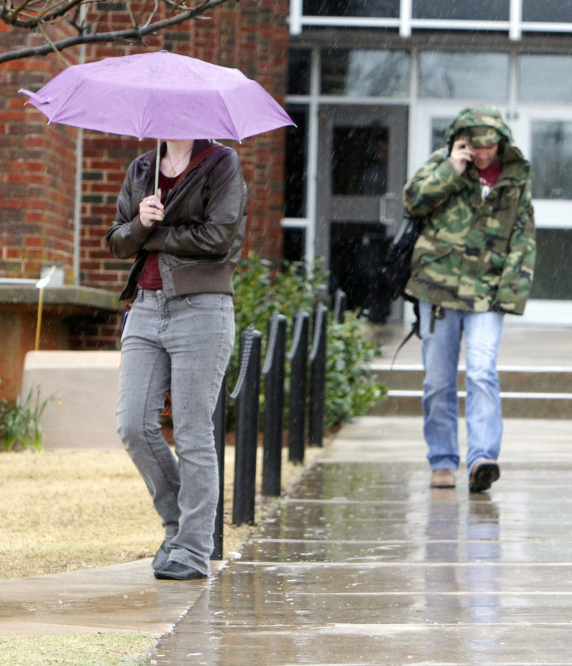 Photo - Students leave classes in the pouring rain Tuesday at the University of Central Oklahoma.  By Paul Hellstern, The Oklahoman  PAUL HELLSTERN - Oklahoman