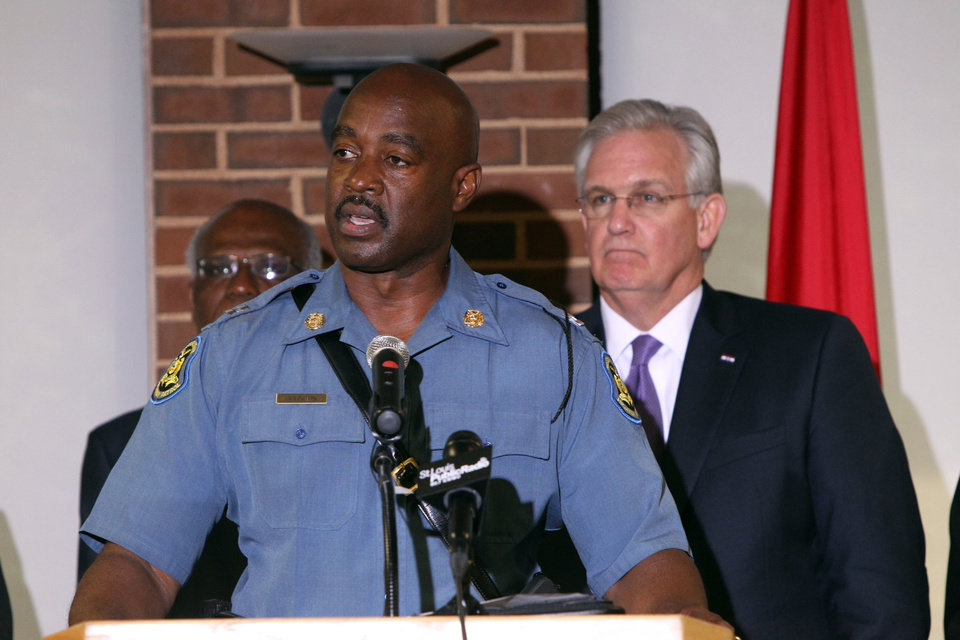 Photo - Missouri Gov. Jay Nixon, right, has given police oversight of the Ferguson situation to the Missouri State Highway Patrol under the command of Capt. Ronald S. Johnson, center, a Ferguson native. Nixon addressed questions from the press at the University of Missouri-St. Louis after touring areas of Ferguson, Thursday, Aug. 14, 2014. (AP Photo/St. Louis Post-Dispatch, Christian Gooden)