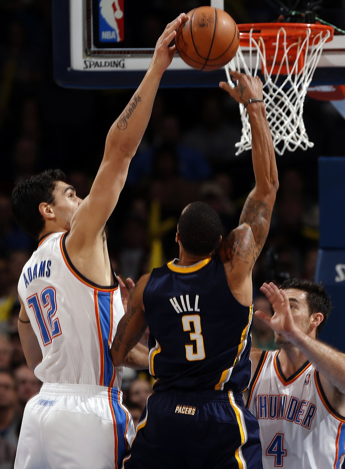 Photo - Oklahoma City's Steven Adams (12) defends against Indiana's George Hill (3) during the NBA game between the Oklahoma City Thunder and the Indiana Pacers at the Chesapeake Energy Arena, Sunday, Dec. 8, 2013. Photo by Sarah Phipps, The Oklahoman