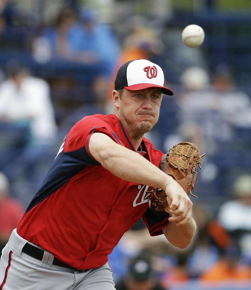 Photo - Washington Nationals starting pitcher Jordan Zimmermann throws to first base in a pickoff attempt of New York Mets' Eric Young Jr. in the first inning of an exhibition spring training baseball game, Thursday, March 27, 2014, in Port St. Lucie, Fla. (AP Photo/David Goldman)