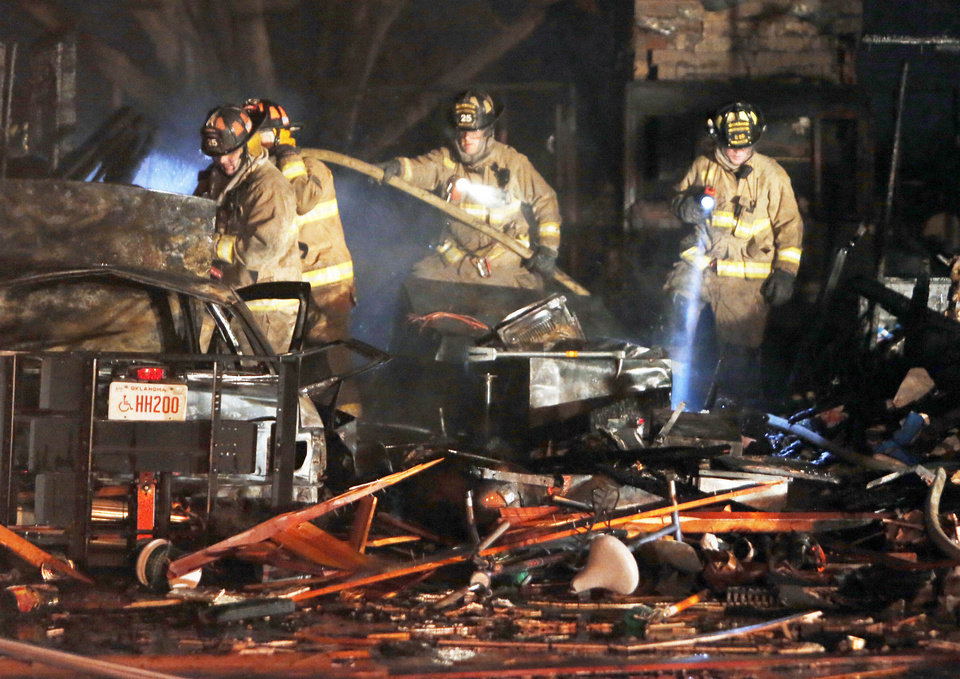 Firefighters examine the interior Thursday of a house destroyed by a natural gas explosion.
