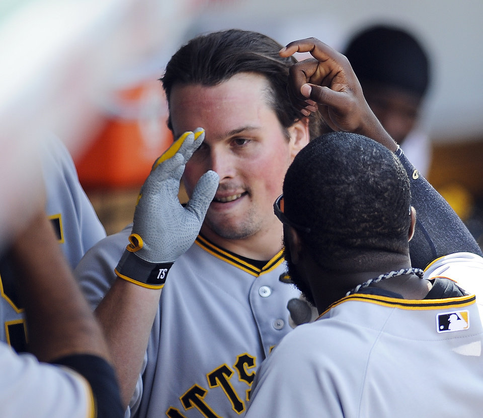 Photo - Pittsburgh Pirates right fielder Travis Snider, center, is congratulated after he homers in the third inning of a baseball game against the Chicago Cubs, Sunday, June 22, 2014, in Chicago. (AP Photo/Matt Marton)