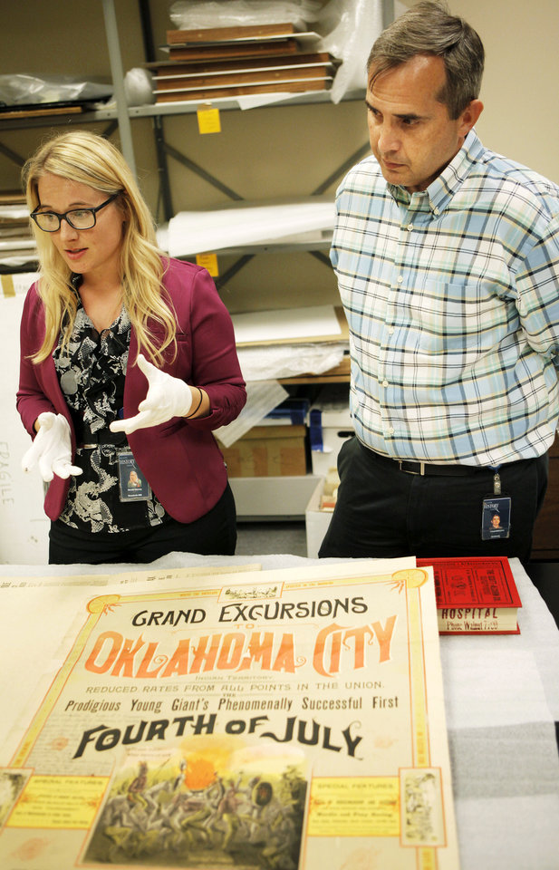 Photo - Nicole Harvey, Oklahoma Historical Society executive assistant (left), and Chad Williams, the Oklahoma Historical Society Director of Research, talk about the rarity and creation of a poster from the 1889 Independence Day celebration in Oklahoma City. The poster will be displayed in an exhibit starting Thursday.  KT King - KT KING
