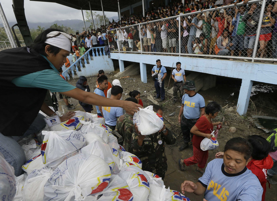 Typhoon victims receive relief goods following the visit of Philippine President Benigno Aquino III at New Bataan township, Compostela Valley in southern Philippines Friday Dec. 7, 2012. More than 310,000 people have lost their homes since Typhoon Bopha struck Tuesday and are crowded inside evacuation centers or staying with their relatives, relying on food and emergency supplies being rushed in by government agencies and aid groups. (AP Photo/Bullit Marquez)