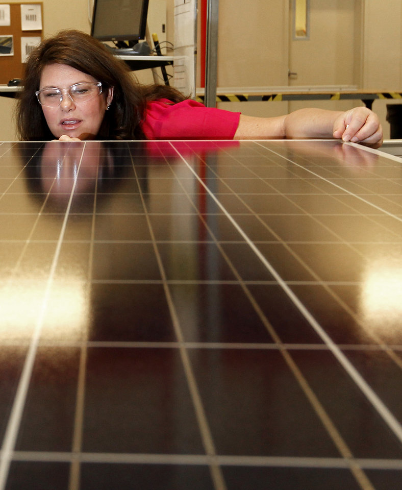 ADVANCE FOR MONDAY, DEC. 3. - In this Sept. 4, 2012 photo, Stacey Rassas, a quality control manager at a Suntech Power Holdings Co., a Chinese-owned solar panel manufacturer, examines a solar panel at a company facility in Goodyear, Ariz. The factory makes solar panels for one of the world's biggest solar manufacturers. (AP Photo/Ross D. Franklin)