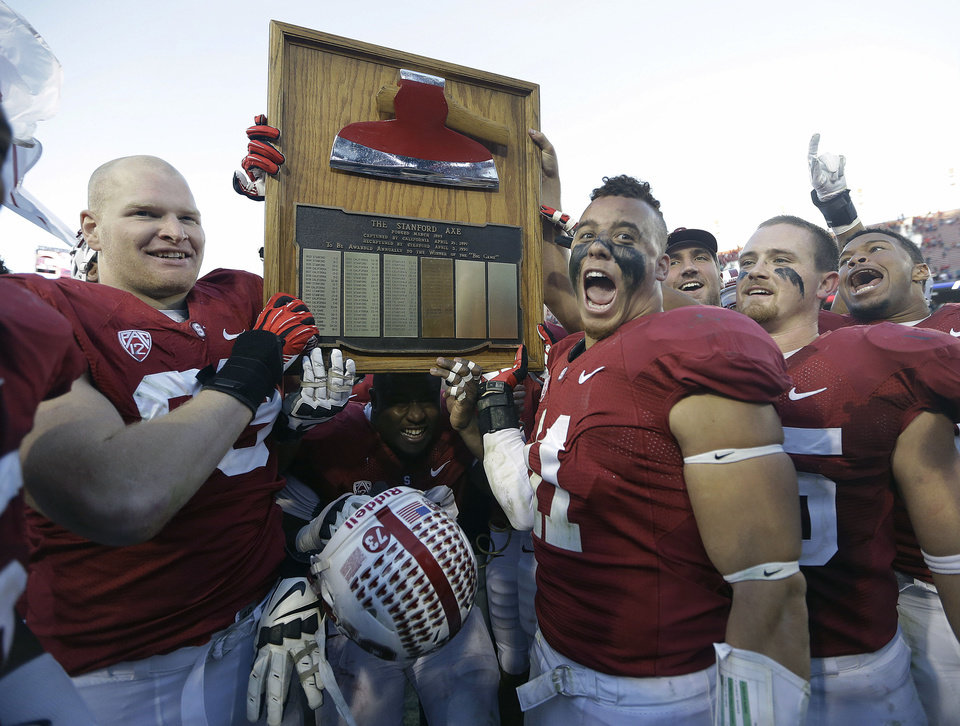 Photo - Stanford's Trent Murphy (93) and Shayne Skov (11) celebrate with The Stanford Axe after a win over California in an NCAA college football game in Stanford, Calif., Saturday, Nov. 23, 2013. Stanford won 65-13. (AP Photo/Tony Avelar)