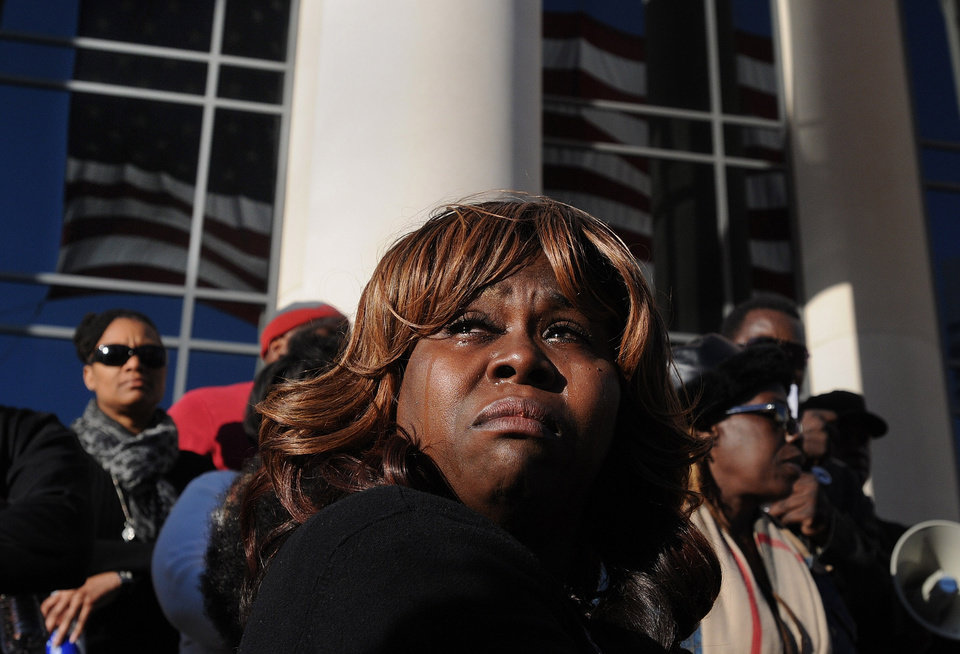 Photo - Denise Hunt tears up as she finds out the jury is deadlocked on the first-degree murder charge for Michael Dunn outside of the Duval County Courthouse as the jury enters the fourth day of deliberations, Saturday, Feb. 15, 2014, in Jacksonville, Fla. Large crowds gathered outside the courthouse to wait for a verdict in the Dunn trial. Dunn was convicted Saturday of attempted murder in the shooting death of a teenager during an argument over loud music, but jurors could not agree on the most serious charge of first-degree murder. (AP Photo/The Florida Times-Union, Kelly Jordan)