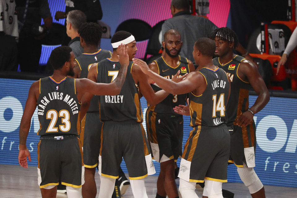 Photo - Oklahoma City Thunder forward Terrance Ferguson (23), forward Darius Bazley (7), guard Chris Paul (3), guard Devon Hall (14) and guard Luguentz Dort (5) celebrate after defeating the Washington Wizards in an NBA basketball game Sunday, Aug. 9, 2020, in Lake Buena Vista, Fla. (Kim Klement/Pool Photo via AP)