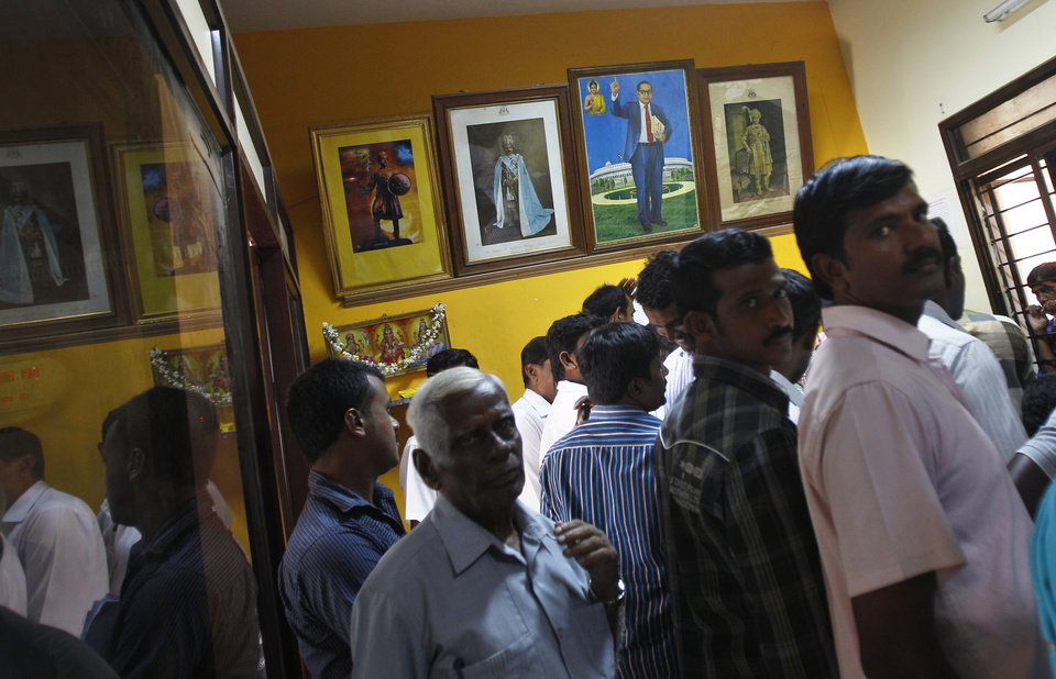 Photo - In this Dec. 10, 2012 photo, a portrait of Bhimrao Ramji Ambedkar, second right, a dalit leader and architect of the Indian Constitution, hangs on the wall inside the government registrar's office as people crowd to get their land registered, in Hoskote 30 kilometers (19 miles) from Bangalore in the southern Indian state of Karnataka. For years, Karnataka's land records were a quagmire of disputed, forged documents maintained by thousands of tyrannical bureaucrats who demanded bribes to do their jobs. In 2002, there were hopes that this was about to change. (AP Photo/Aijaz Rahi)