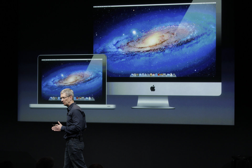 FILE - In this Tuesday, Oct. 4, 2011, file photo, Apple CEO Tim Cook  speaks in front of a projection of the Macbook Air and Mac Desktop during announcement at Apple headquarters in Cupertino, Calif. Apple CEO Tim Cook said Thursday the company will produce one of its existing lines of Mac computers in the United States next year. Like most consumer electronics companies, Apple forges agreements with contract manufacturers to assemble its products overseas.  (AP Photo/Paul Sakuma, File)