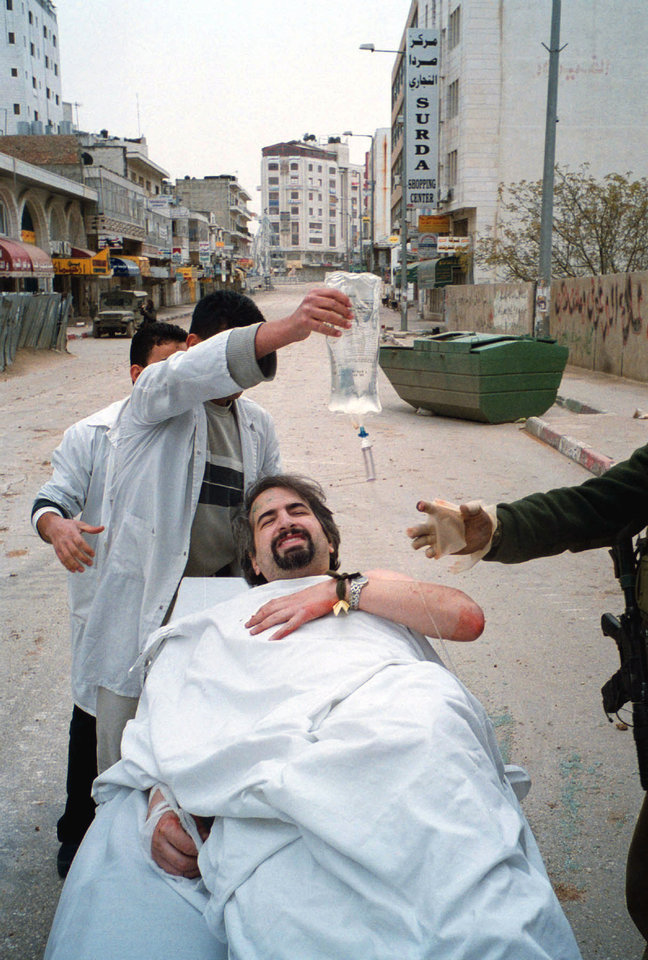Photo - Boston Globe reporter Anthony Shadid receives assistance from Palestinian doctors and Israeli medics after being shot in the shoulder while reporting in the West Bank city of Ramallah March 31, 2002. Shadid had been shot in the West Bank in 2002 and kidnapped for six days in Libya last year, but it was an apparent asthma attack that killed the two-time Pulitzer Prize winner in Syria Thursday Feb. 16, 2012while he was reporting on the uprising against its president.  (AP Photo/Michael Robinson Chavez, The Washington Post) ORG XMIT: DCWAP101