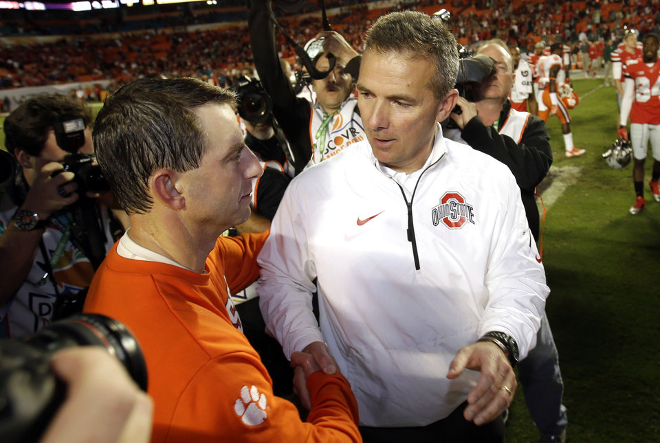 Photo - Ohio State head coach Urban Meyer, right, shakes hands with Clemson head coach Dabo Swinney after the Orange Bowl NCAA college football game, Saturday, Jan. 4, 2014, in Miami Gardens, Fla. Clemson defeated Ohio State 40-35.  (AP Photo/Wilfredo Lee)
