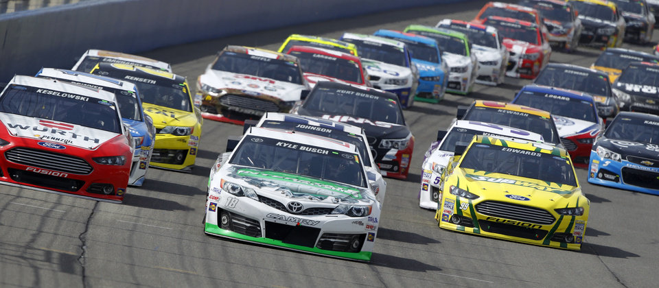 Photo - Kyle Busch (18) leads the pack during a restart after a caution flag during the NASCAR Sprint Series auto race in Fontana, Calif., Sunday, March 23, 2014. Busch won the race. (AP Photo/Alex Gallardo)