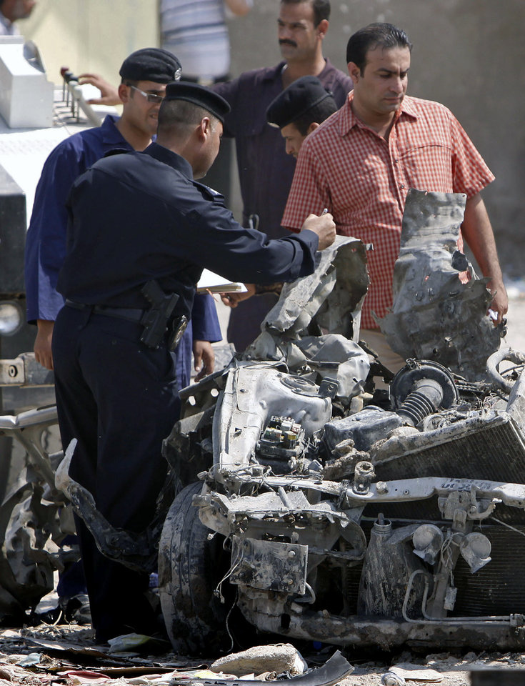 Photo -   Security forces inspect the scene of a car bomb attack in Basra, 340 miles (550 kilometers) southeast of Baghdad, Iraq, Sunday, Sept. 9, 2012. In violence, which struck at least 10 cities across the nation Insurgents killed at least 39 people in a wave of attacks against Iraqi security forces on Sunday, gunning down soldiers at an army post and bombing police recruits waiting in line to apply for jobs, officials said. (AP Photo/Nabil al-Jurani)