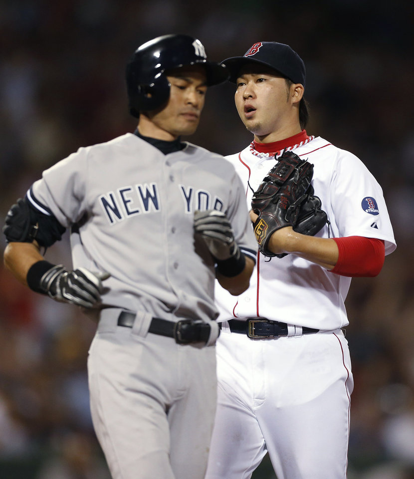 Photo - New York Yankees' Ichiro Suzuki, left, passes Boston Red Sox's Junichi Tazawa after grounding out to end the top of the seventh inning of a baseball game in Boston, Sunday, July 21, 2013. (AP Photo/Michael Dwyer)