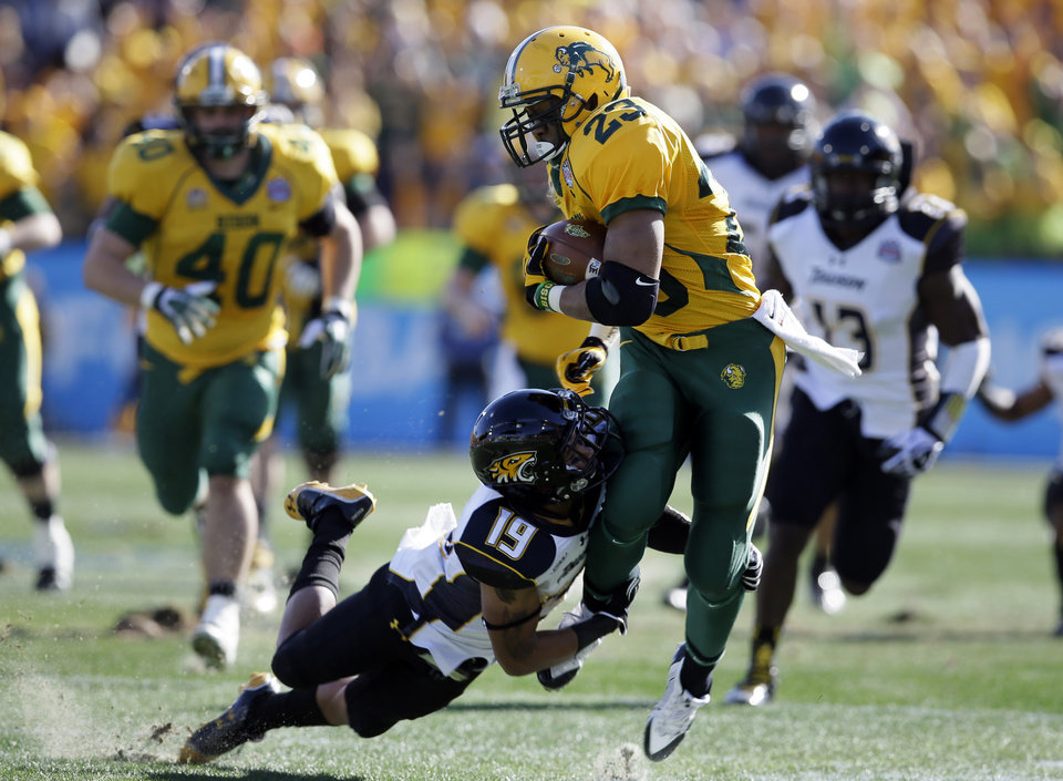 Photo - North Dakota State running back John Crockett (23) fights for extra yardage as Towson cornerback Juleon Killikelly-Lee (19) attempts the tackle in the first half of the FCS championship NCAA college football game, Saturday, Jan. 4, 2014, in Frisco, Texas. (AP Photo/Tony Gutierrez)