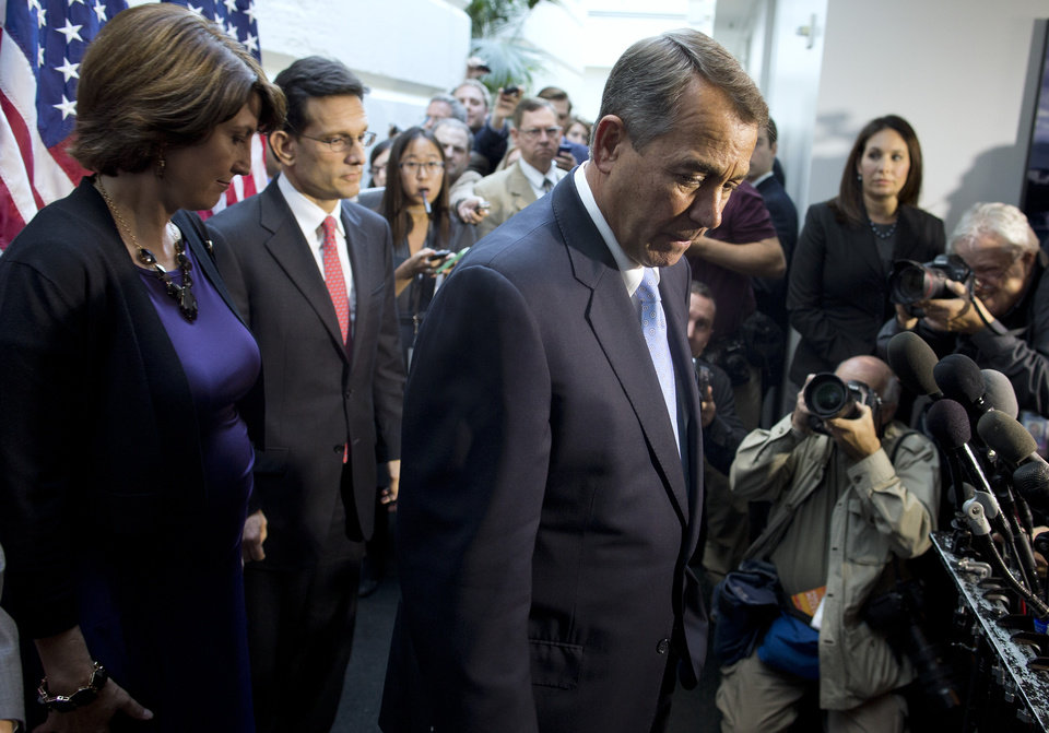 Photo - Speaker of the House Rep. John Boehner, R-Ohio, pauses during a news conference after a House GOP meeting on Capitol Hill on Tuesday, Oct. 15, 2013 in Washington. House GOP leaders Tuesday floated a plan to fellow Republicans to counter an emerging Senate deal to reopen the government and forestall an economy-rattling default on U.S. obligations. But the plan got mixed reviews from the rank and file and it was not clear whether it could pass the chamber. (AP Photo/ Evan Vucci)