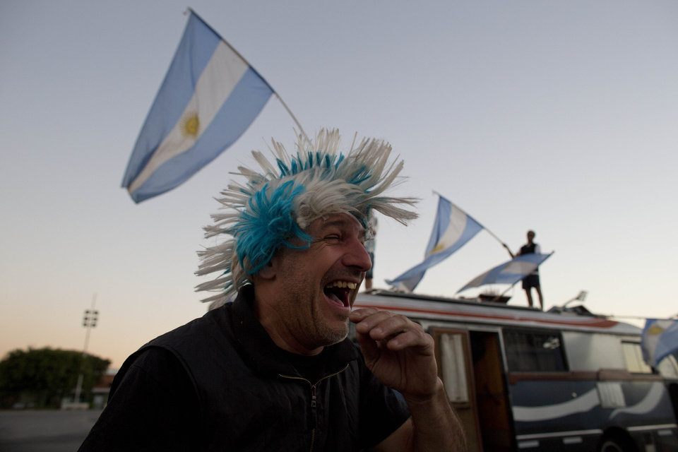 Photo - An Argentine fan laughs as he stands next to his recreational vehicle at the Samabdrome during the 2014 soccer World Cup in Sao Paulo, Brazil, Monday, June 30, 2014. Argentina will face Switzerland on Tuesday for a second stage match of the World Cup. (AP Photo/Dario Lopez-Mills)