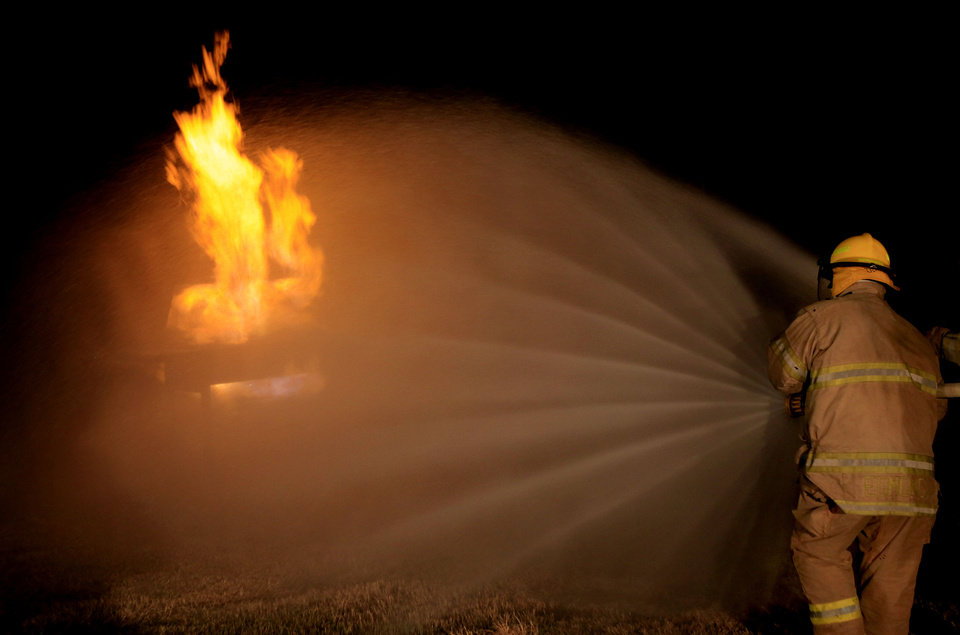 One of the Citizens Fire Academy participants puts out a gas grill fire during the Edmond Fire Department's live firefighting training. PHOTO BY SARAH PHIPPS, THE OKLAHOMAN. <strong>SARAH PHIPPS - THE OKLAHOMAN</strong>