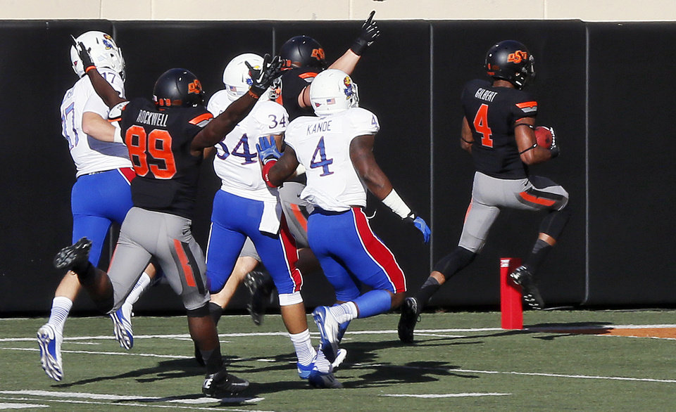 Oklahoma State's Justin Gilbert (4) takes the opening kickoff for a touchdown during a college football game between the Oklahoma State University Cowboys (OSU) and the University of Kansas Jayhawks (KU) at Boone Pickens Stadium in Stillwater, Okla., Saturday, Nov. 9, 2013. Photo by Nate Billings, The Oklahoman