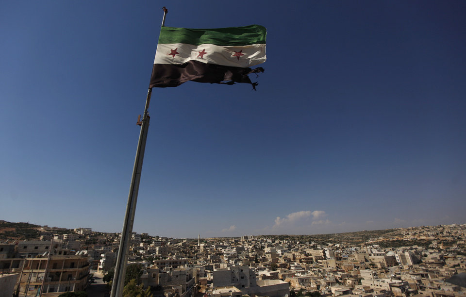 Photo -   FILE - This June 12, 2012 file photo shows a Syrian revolutionary flag waving on top of a building on the outskirts of Aleppo, Syria. Syria's conflict is the most violent to emerge from last year's Arab Spring. The protests started peacefully but prompted a brutal crackdown by President Bashar Assad's government. The fighting has escalated into a civil war that has killed just over 30,000 people over the last year and a half, according to activists. Despite intervening in Libya, the United States has steered clear of taking military action or arming Syria's rebels. (AP Photo/Khalil Hamra, File)