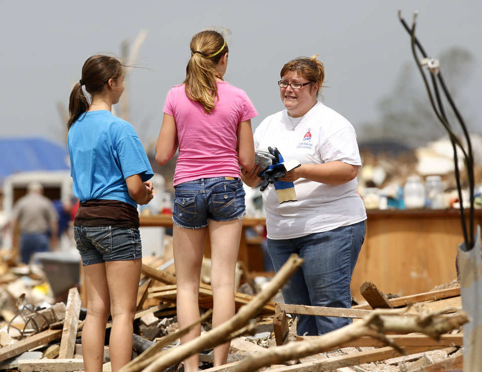 Photo - Linda Feagan, 12, center, and her best friend, Remi Long, are thanked by a tornado survivor after the girls ran over to where they were working and handed them several pairs of work gloves.  The two girls are part of a  group that came from the north Dallas area to help refresh volunteers. The bed of their truck was filled with cold beverages and light food, including beef jerky. They also brought a trailer loaded with toiletries and gloves to distribute. They are from a small town called Blue Ridge and they said the community  organized a drive earlier in the week requesting donated items for the relief effort. Volunteers from various parts of the country joined Oklahomans in assisting residents on Saturday,  May 25, 2013, doing whatever was needed to remove debris and salvage items from this neighborhood east of Santa Fe, north of SW 19 Street.  An EF5 tornado leveled many neighborhoods in Moore and southwest Oklahoma City last Monday.   Photo  by Jim Beckel, The Oklahoman.