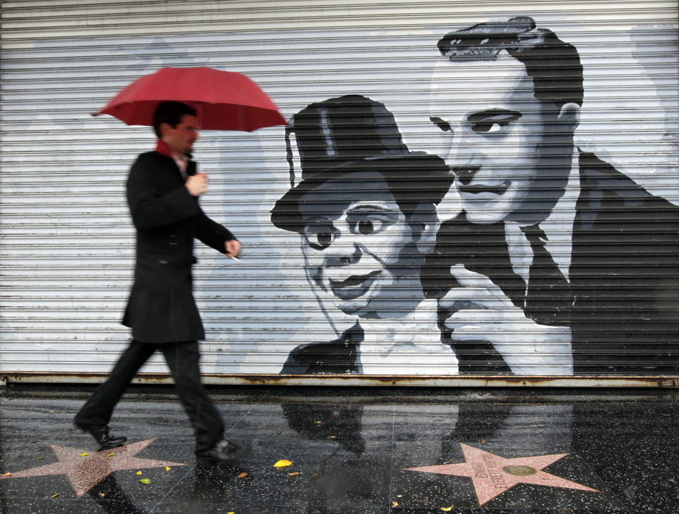 A pedestrian passes by a mural showing iconic comedy team Charlie McCarthy and  Edgar Bergan during a rainstorm in the Hollywood section of Los Angeles Friday, Nov. 30, 2012. A series of storm systems will continue to move across southwestern California through Monday morning. (AP Photo/Damian Dovarganes)