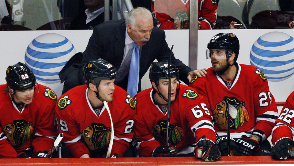 Photo - FILE - In this Jan. 27, 2013, file photo, Chicago Blackhawks head coach Joel Quenneville talks to Viktor Stalberg (25) as Patrick Kane (88), Bryan Bickell (29) and Andrew Shaw (65) sit by late in the third period of an NHL hockey game against the Detroit Red Wings in Chicago. Forward Patrick Sharp says Quenneville has played a key role in the team's record-breaking start. Chicago has at least one point in each of its first 19 games and puts the streak on the line Thursday night in St. Louis. (AP Photo/John Smierciak, File)