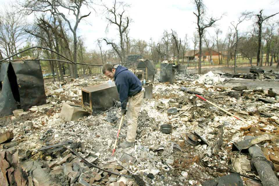 Photo - Sean Feroli searches for antique coins in the ashes of his father in-laws home at 347 Ash road that was destroyed in a wildfire in Choctaw, Oklahoma April 10, 2009.  Photo by Steve Gooch, The Oklahoman