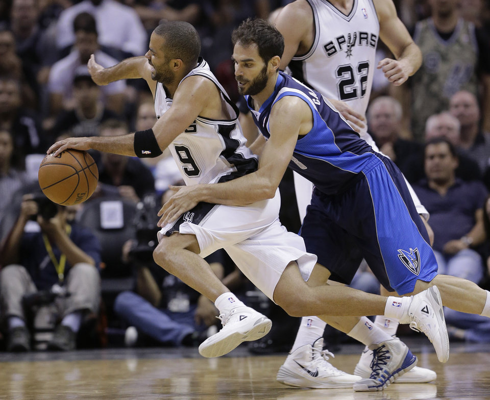 Photo - San Antonio Spurs' Tony Parker (9), of France, is fouled by Dallas Mavericks' Jose Calderon (8), of Spain, during the second half of Game 5 of the opening-round NBA basketball playoff series on Wednesday, April 30, 2014, in San Antonio. San Antonio won 109-103. (AP Photo/Eric Gay)