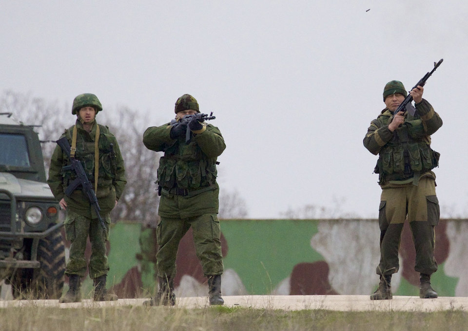Photo - Russian soldiers fire warning shots at the Belbek air base, outside Sevastopol, Ukraine, on Tuesday, March 4, 2014. Russian troops, who had taken control over Belbek airbase, fired warning shots in the air as around 300 Ukrainian officers marched towards them to demand their jobs back. (AP Photo/Ivan Sekretarev)