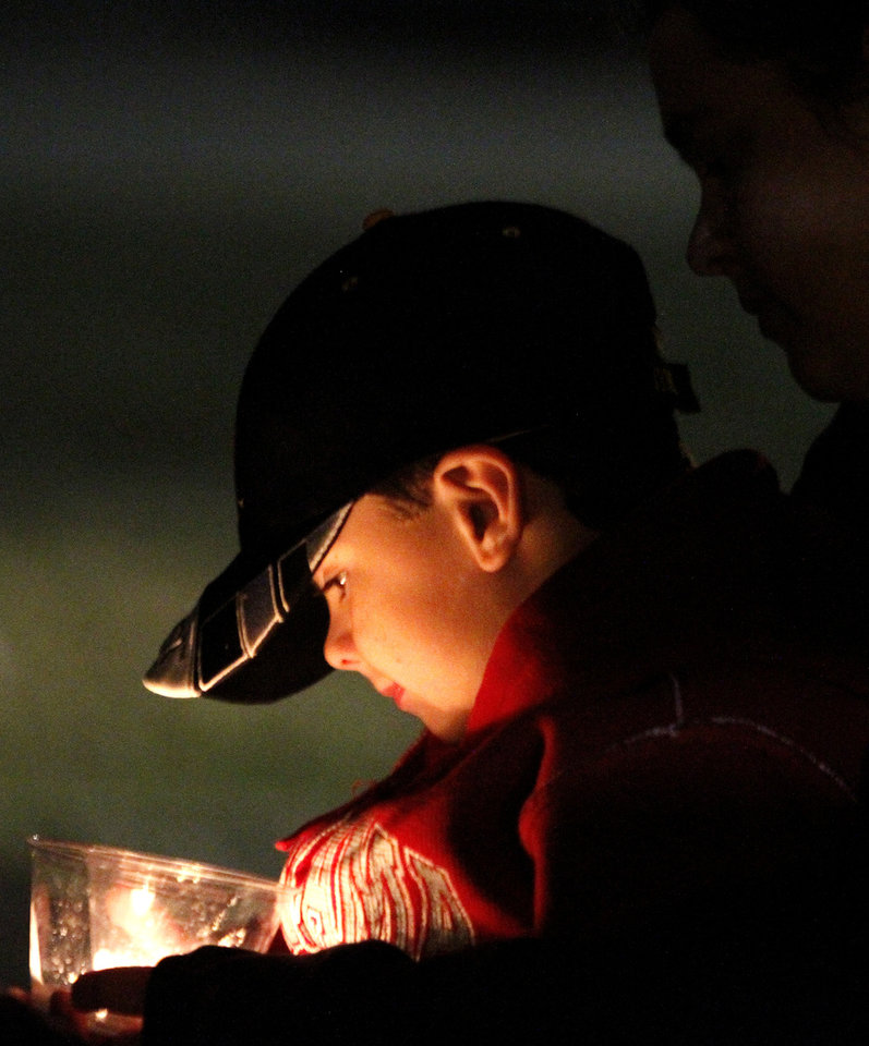 Cole Wyatt watches the candle flicker as he sits with his mom, Sheree Wyatt, as friends gather to pray for a 5-year-old taken hostage, in Midland City, Ala., Sunday, Feb. 3, 2013. Authorities say Jim Lee Dykes, 65 — a decorated Vietnam-era veteran known as Jimmy to neighbors — gunned down a school bus driver and then abducted a 5-year-old boy from the bus, taking him to an underground bunker on his rural property. The driver, 66-year-old Charles Albert Poland Jr., who was shot trying to protect children on his bus, was buried Sunday. (AP Photo/Butch Dill)
