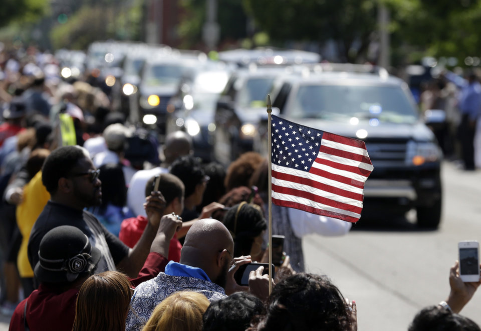 Photo - A mourner holds an American flag as the funeral procession for Muhammad Ali makes its way down Muhammad Ali Boulevard in Louisville, Ky. Friday, June 10, 2016. (AP Photo/Michael Conroy)