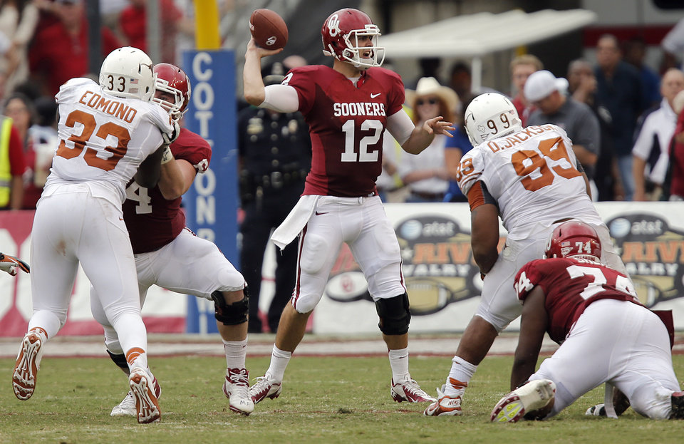 Photo - OU's Landry Jones (12) passes the ball during the Red River Rivalry college football game between the University of Oklahoma (OU) and the University of Texas (UT) at the Cotton Bowl in Dallas, Saturday, Oct. 13, 2012. Photo by Chris Landsberger, The Oklahoman