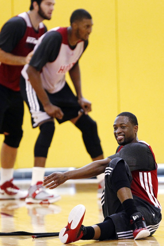 Photo -   Miami Heat guard Dwyane Wade, bottom right,, stretches during NBA basketball practice, Monday, Oct. 1, 2012, in Miami. In many ways, the Heat think they're picking up in training camp where they left off in June. And that's one of many reasons why confidence around the reigning NBA champions is high these days. (AP Photo/Wilfredo Lee)