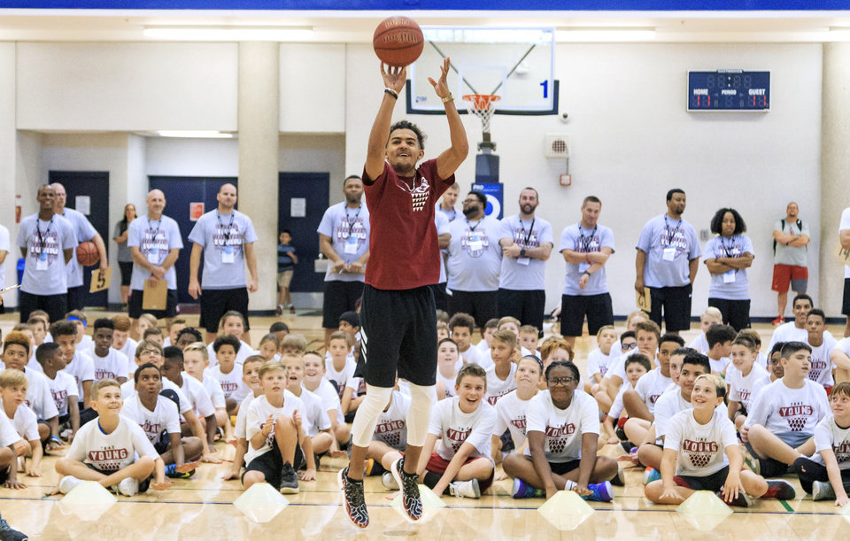 Photo -  Trae Young puts up a three point shot as he put on a demonstration for participants during the Trae Young Basketball Pro Camp at the University of Oklahoma's Sarkeys Fitness Center in Norman on Wednesday. [PHOTO BY CHRIS LANDSBERGER, THE OKLAHOMAN]