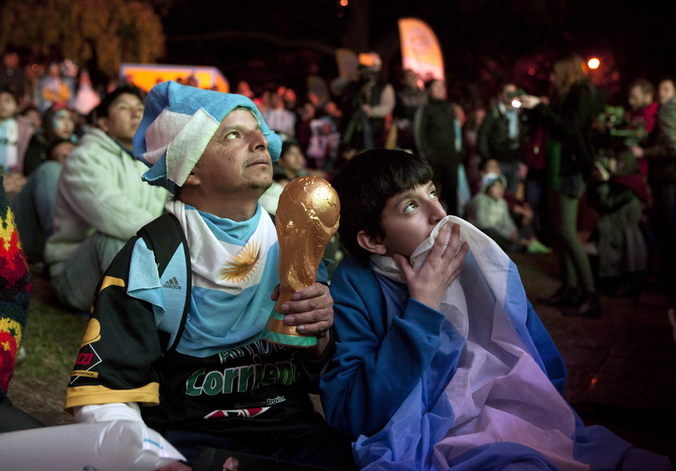Photo - An Argentina soccer fan holds a replica of the World Cup trophy while watching the World Cup game between Argentina and Bosnia with others gathered before an outdoor screen set up in Buenos Aires, Argentina, Sunday, June 15, 2014. (AP Photo/Eduardo Di Baia)