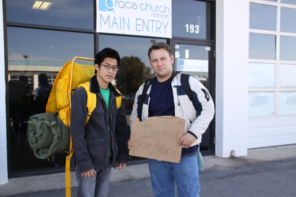 Photo - Philip Nguyen, left, and Dusty Buff, pastor of Grace Church in Norman, stand outside their church before leaving for a 10-day sojourn among the homeless. Buff's sign reads,