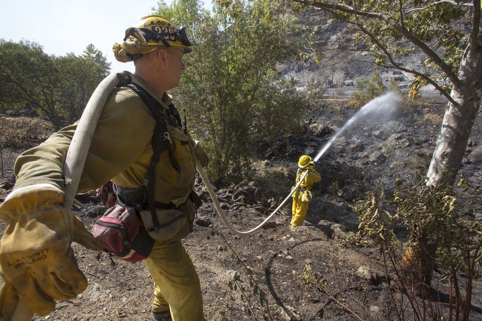 Photo - Firefighters douse a burned area along the hillside near the student dorm of  Cal State, Channel Islands in Camarillo, Calif., Thursday, May 2, 2013. (AP Photo/Ringo H.W. Chiu)