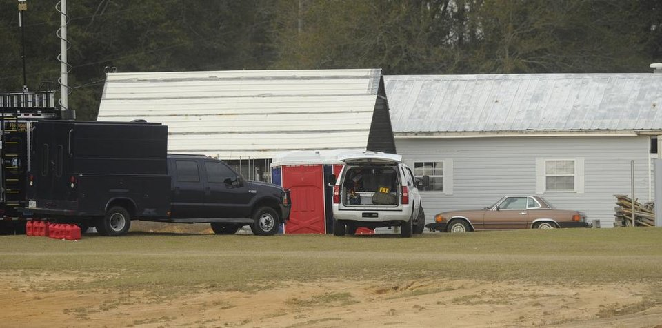 Photo - Law enforcement personnel station themselves on the property of Jimmy Lee Sykes, Monday, Feb. 4, 2013 in Midland City, Ala. Officials say they stormed a bunker in Alabama to rescue a 5-year-old child being held hostage there after Sykes, his abductor, was seen with a gun. (AP Photo/AL.com, Joe Songer)