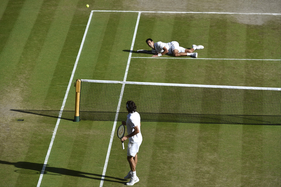 Photo - Novak Djokovic of Serbia, top, falls onto the court during the men's singles final against Roger Federer of Switzerland at the All England Lawn Tennis Championships at Wimbledon, London, Sunday July 6, 2014. (AP Photo/Toby Melville, Pool)