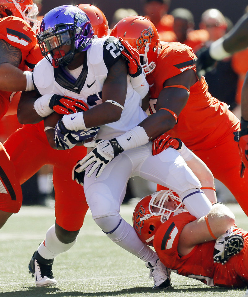 OSU defenders stop TCU's B.J. Catalon (23) during a college football game between the Oklahoma State University Cowboys (OSU) and the Texas Christian University Horned Frogs (TCU) at Boone Pickens Stadium in Stillwater, Okla., Saturday, Oct. 19, 2013. Photo by Nate Billings, The Oklahoman