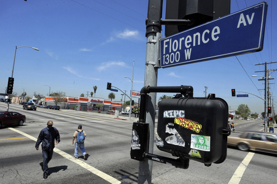 Photo -   This April 17, 2012 photo shows street signs at the intersection of Florence and Normandie Avenues in South-Central Los Angeles. The intersection was the location of much of the early violence in the Los Angeles riots that began on April 29, 1992, beginning with the beating of truck driver Reginald Denny. The acquittal of four police officers in the videotaped beating of Rodney King sparked rioting that spread across the city and into neighboring suburbs. Cars were demolished and homes and businesses were burned. Before order was restored, 55 people were dead, 2,300 injured and more than 1,500 buildings were damaged or destroyed. (AP Photo/Chris Pizzello)