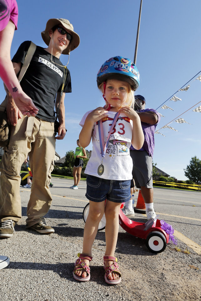 Photo -  Brooklyn Phillips, 3, receives a medal Saturday as her father Kyle Phillips watches at The Ride, a race in Norman that raised money for United Way. PHOTO BY STEVE SISNEY, THE OKLAHOMAN   STEVE SISNEY -