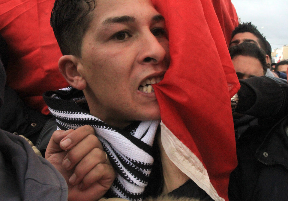 Photo - A Tunisian bites the national flag while carrying the coffin of slain Tunisian opposition leader Chokri Belaid during his funeral in Tunis, Friday, Feb. 8, 2013. Tunisia braced for clashes on Friday, with the capital shut down by a general strike and the army deployed for the funeral of a slain opposition leader expected to draw tens of thousands of mourners, and potentially many more. (AP Photo/Amine Landoulsi)