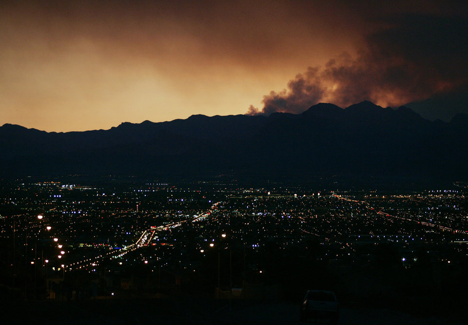 Smoke from the Mount Charleston wildfires hovers over the Las Vegas valley shortly after sunset Tuesday, July 9, 2013, in Las Vegas. The fire, which started by lighting July 1, has consumed nearly 20,000 acres as of Tuesday evening. Firefighters expect to have it contained by July 19. (AP Photo/ Ronda Churchill)