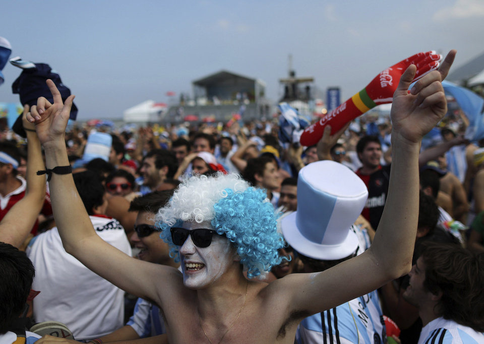 Photo - Argentine soccer fans get revved up before the live telecast of the World Cup round of 16 match between Argentina and Switzerland, at the FIFA Fan Fest area on Copacabana beach in Rio de Janeiro, Brazil, Tuesday, July 1, 2014. (AP Photo/Leo Correa)